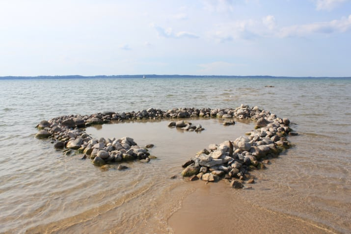 What it means everywhere else: A mass of sand accompanying an ocean.What it means in the Midwest: Sand around a lake. Or rocks. We aren\'t very picky.